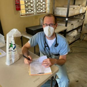 Image showing Dr. Jim McCann writing notes in a patient's chart. El Naranjito, 2021.